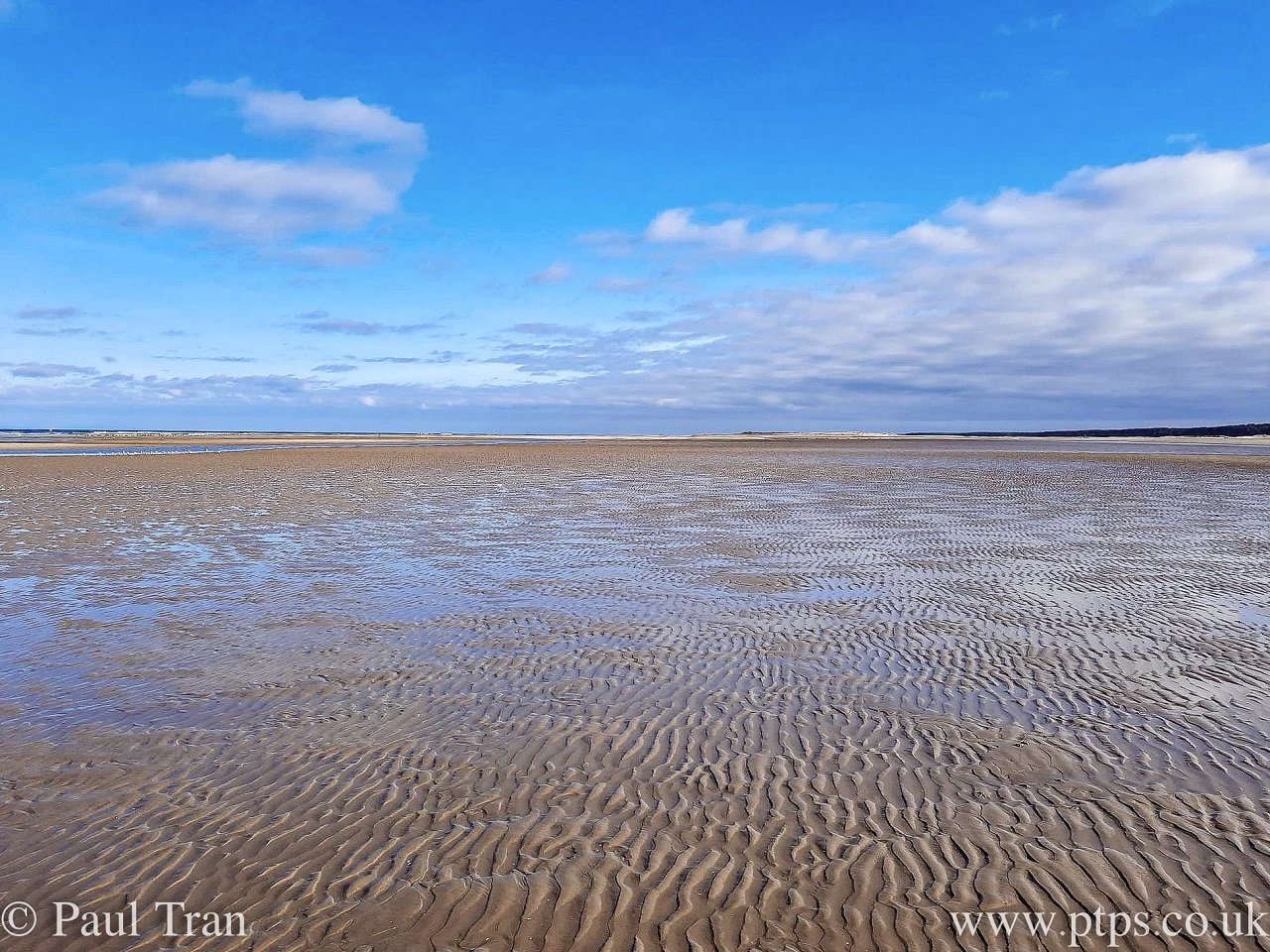 beach at low tide under a blue sky with a few small clouds
