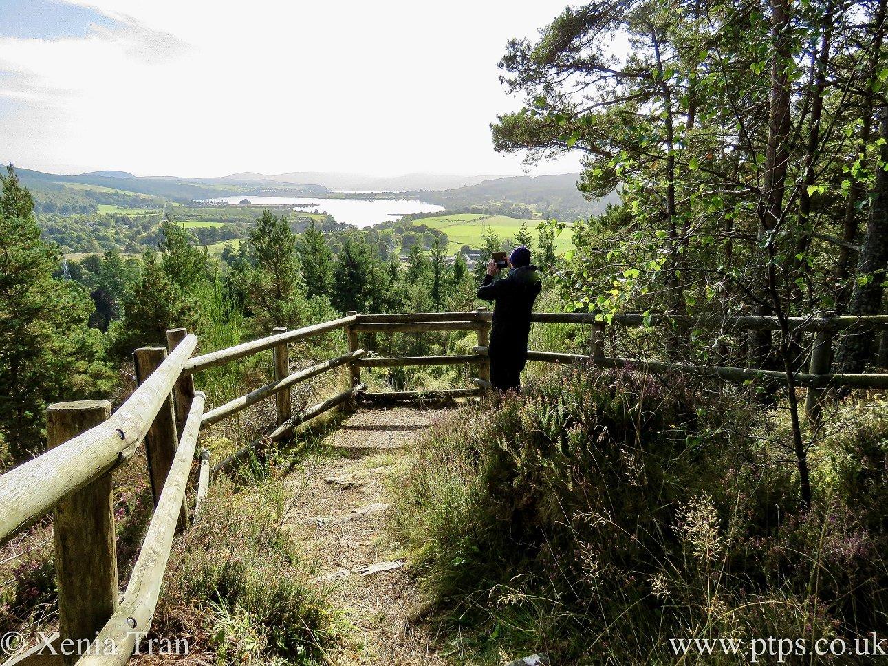 Paul Tran taking a photograph at a viewpoint