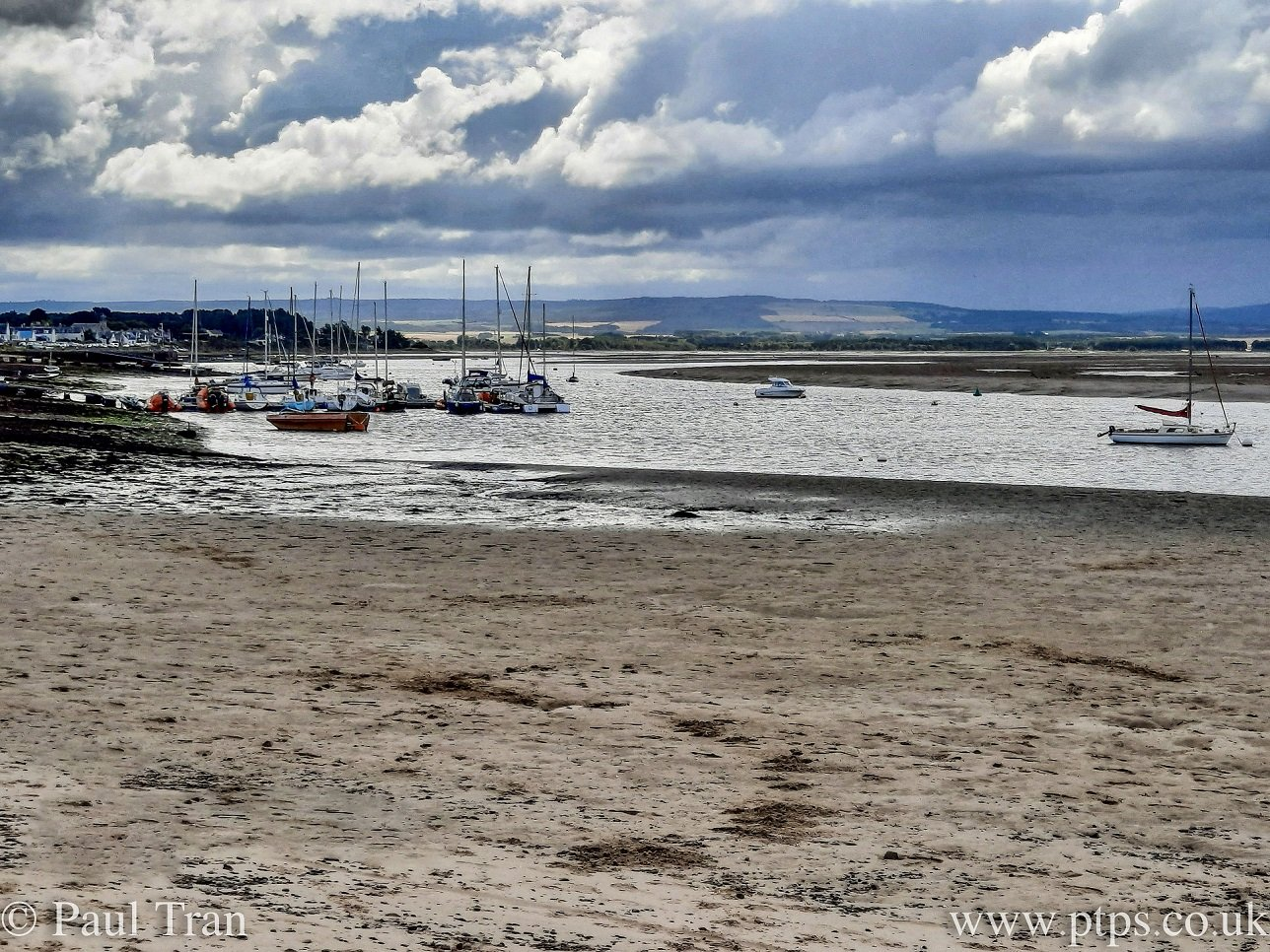 sailing boats anchored and moored in Findhorn Bay at low tide